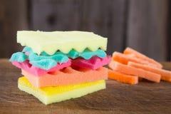 Hamburger van sponsen verschillende kleuren wordt gemaakt op houten bacground die Concept ongezond voedsel en niet natuurlijke pr Stock Afbeelding