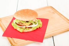 Hamburger with vegetables, on wooden table. Home made hamburger with onion, tomato, lettuce, cheese . close-up Stock Image