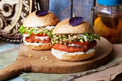 Hamburger vegetariano con il taglio del cece e la poltiglia germinata in una natura morta su un alimento di legno della casa del  fotografia stock