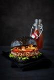 Hamburger w czarnego chleba ketchupie i babeczkach zdjęcie stock