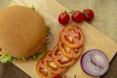 Hamburger wird mit gegrilltem Schweinefleisch, K?se, Tomaten, Kopfsalat und Zwiebeln auf einem rechteckigen Bretterboden zugebere stockbild