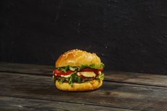 Hamburger on a wooden board against a dark background with copy space. Hamburger with sauce and fresh vegetables on a wooden table royalty free stock images