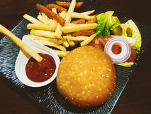 Hamburger on wooden table on a black plate. Stock Photos