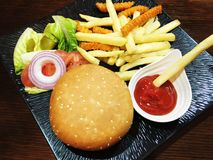 Hamburger on wooden table on a black plate. Royalty Free Stock Photos