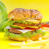 Hamburger on yellow background. Big tasty hamburger on yellow background Stock Photo