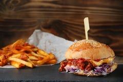 Hamburger z coleslaw i serem na drewnie i d?oniakach autentyczny domowej roboty hamburger z obrazy stock