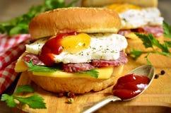 Hamburger z serem, salami i smażącym jajkiem, Zdjęcia Royalty Free