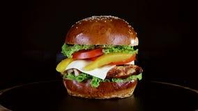 Hamburger z wielkim kawałkiem mięso, zielenie i ser, wirujemy na drewnianej desce na czarnym tle zbiory wideo