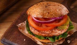 Hamburger zamknięty up na tnącej desce na drewnianym tle Obraz Stock