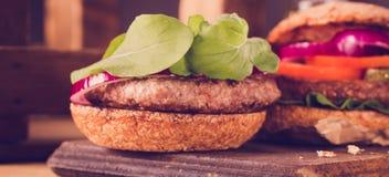 Hamburger zamknięty up na tnącej desce na drewnianym tle Obrazy Royalty Free