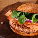 Hamburger zamknięty up na tnącej desce na drewnianym tle Obraz Royalty Free