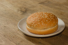 Hamburgerbroodje op de houten lijst Stock Foto's