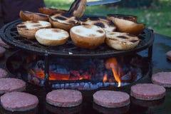 Hamburgerfleisch und -brötchen werden auf dem Grill gegrillt Außerhalb des Kochens und des Grills Mahlzeit auf dem Grill Hamburge lizenzfreie stockbilder