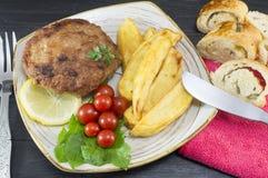 Hamburgerlapje vlees met aardappels, kersentomaten en olijfbrood o Royalty-vrije Stock Foto