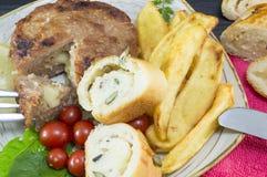 Hamburgerlapje vlees met aardappels, kersentomaten en olijfbrood o Stock Fotografie