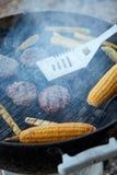 Hamburgerpasteitjes en graan op een hete barbecuegrill stock afbeelding