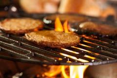 Hamburgerpastetchen auf einem Grill mit Feuer darunter Stockfotos