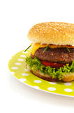 Hamburgers. Tasty cheeseburgers with vegetables on a dotted plate royalty free stock photography