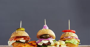 Hamburgers arranged in a row. Against grey background stock video footage