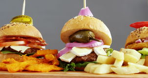 Hamburgers arranged in a row. Against grey background stock video