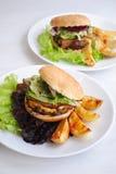 Hamburgers avec la côtelette de boeuf, la salade et les pommes de terre cuites au four Photo libre de droits