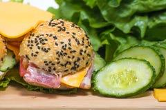 Hamburgers avec les légumes et le lard sur le bureau en bois Image libre de droits