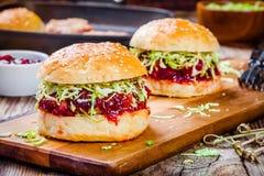 Hamburgers avec une côtelette de dinde, de sauce à la canneberge et de salade Photographie stock libre de droits