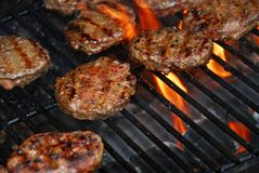 Hamburgers on barbeque. Hamburgers cooking on barbeque grill with flames Royalty Free Stock Image