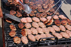Hamburgers on barbeque. Hamburgers cooking on barbeque grill and palettes who turn not to burn Stock Photo