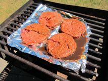 Hamburgers beef meat grilled barbecue outdoors. Hamburgers beef meat grilled barbecue outdoor cookout Royalty Free Stock Image