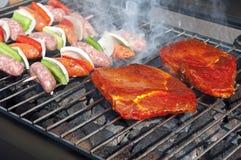 Hamburgers, boeuf et saucisses sur un gril avec des flammes image libre de droits