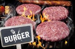 Hamburgers, boeuf et saucisses sur un gril avec des flammes images stock