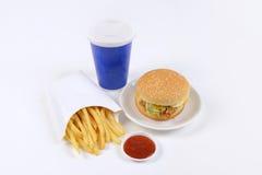 Hamburgers contenants figés d'aliments de préparation rapide, pommes frites et boisson non alcoolisée d'isolement sur le fond bla Photographie stock libre de droits