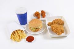 Hamburgers contenants figés d'aliments de préparation rapide, poulet frit, pommes frites et boisson non alcoolisée d'isolement su Photos libres de droits