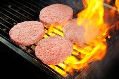 Hamburgers crus de boeuf étant faits cuire Photos stock