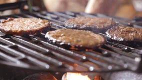 Hamburgers crus sur le gril de barbecue avec le feu banque de vidéos