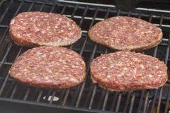 Hamburgers crus sur un barbecue Photos libres de droits