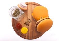 Hamburgers d'isolement sur le fond blanc et la table en bois Photographie stock