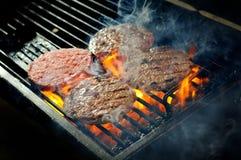 Hamburgers de boeuf étant faits cuire Images libres de droits