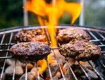 Hamburgers de boeuf faisant cuire sur le gril extérieur Photo stock