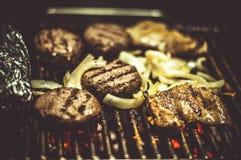 Hamburgers et friture de légumes sur le gril Photo stock