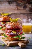 Hamburgers faits maison avec le petit pain entier de grain, le lard frit et les poivrons marinés épicés Photographie stock libre de droits