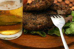 Hamburgers and fork. Hamburgers on wooden plate with beer Stock Photo