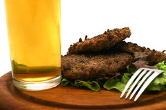 Hamburgers fork and beer. Beer with hamburgers and fork on plate Stock Photos