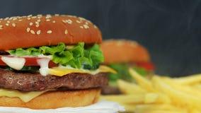 Hamburgers frais et pommes frites grillés faits maison tournant sur le fond noir de fumée Petit pâté de viande, tomates, concombr clips vidéos