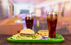 Hamburgers, french fries with sauce, cola on green spacing. Hamburgers, french fries with sauce and cola on green spacing Stock Photo