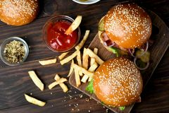 Hamburgers and french fries. On wooden table. Top view, flat lay Royalty Free Stock Photo