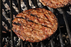 Hamburgers on the grill. Hamburgers cooking on the grill, copy space Stock Photography