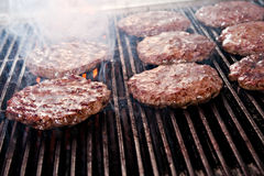 Hamburgers on the grill. A group of cooking hamburgers on the grill Royalty Free Stock Photos
