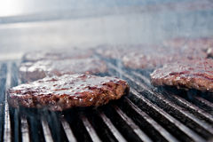 Hamburgers on the grill. A group of cooking hamburgers on the grill Royalty Free Stock Images